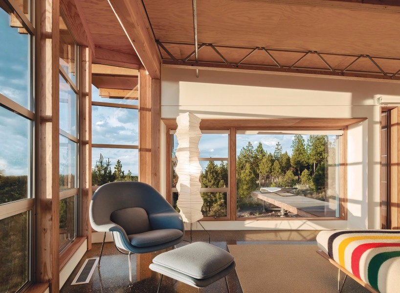 In the master bedroom of this modular prefab in Oregon, a Womb chair and ottoman, an Isamu Noguchi Akari lamp, and forest views make for a cozy reading nook.
